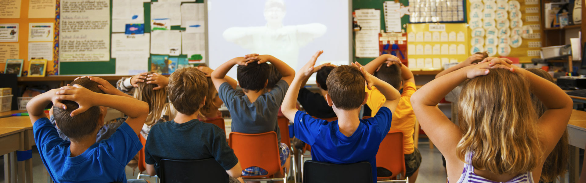 Kids in the classroom watching a presentation at the front of the class on the projection screen